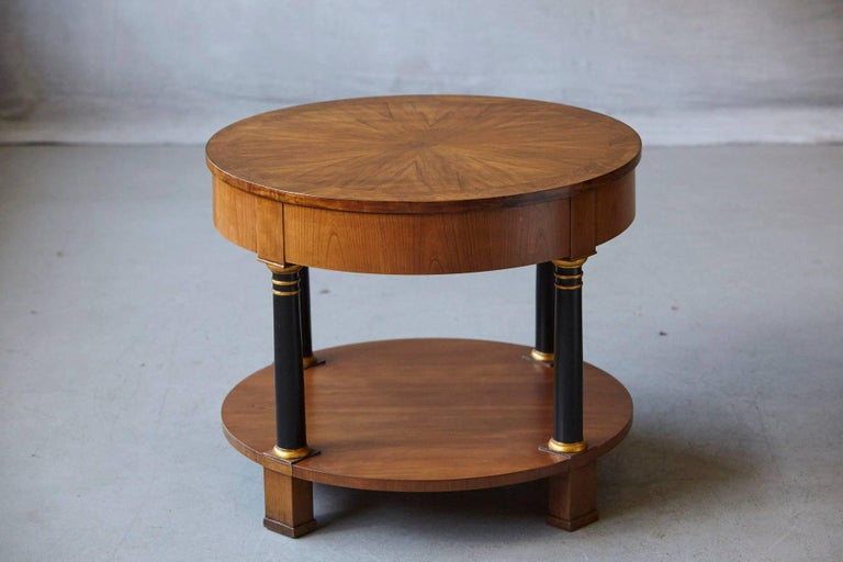Very fine round Empire style two-tier walnut side or end table with one drawer by Baker Furniture, circa 1970s. Sunburst walnut veneer top, black lacquered columns with guilt accents. Drawer with original brass hardware. The Baker metal sign on the