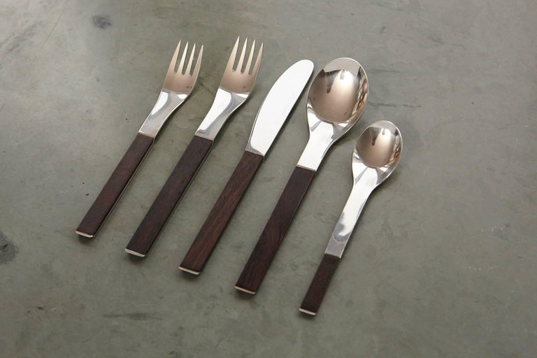 Exceptional rosewood and stainless steel flatware set 'Duo' for 12 place settings designed by Carl Auböck and made by Amboss Neuzeug Hammer Company for Rosenthal Austria, circa 1967. Each set is composed of five pieces (fork, knife, spoon, salad or