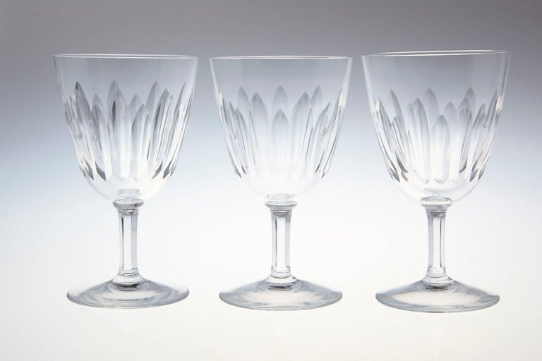 Rare set of eight Baccarat crystal white wine glasses in the 'Verone' pattern. The glasses are in a vertical cut bowl form with a six sided stem. This pattern was manufactured between 1954-1961.