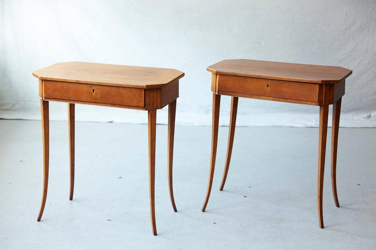 Beautiful pair of light and airy Biedermeier side tables with elegant sabre legs, single drawer and maple veneer.  Both tops are slightly bend, please refer to the detailed photos. Please note the keys for the locks are available, we just forgot to