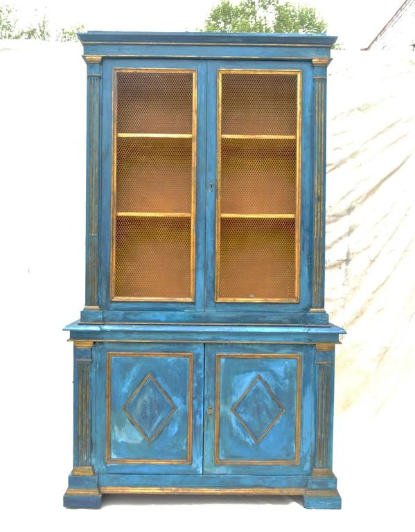 A spectacular mid-20th century Italian two-piece breakfront in striking mediterranean blue plaster. The top having gilt accented moldings, stop-reeded flanking moldings which encase the two large chicken-wired doors which open to reveal a spacious