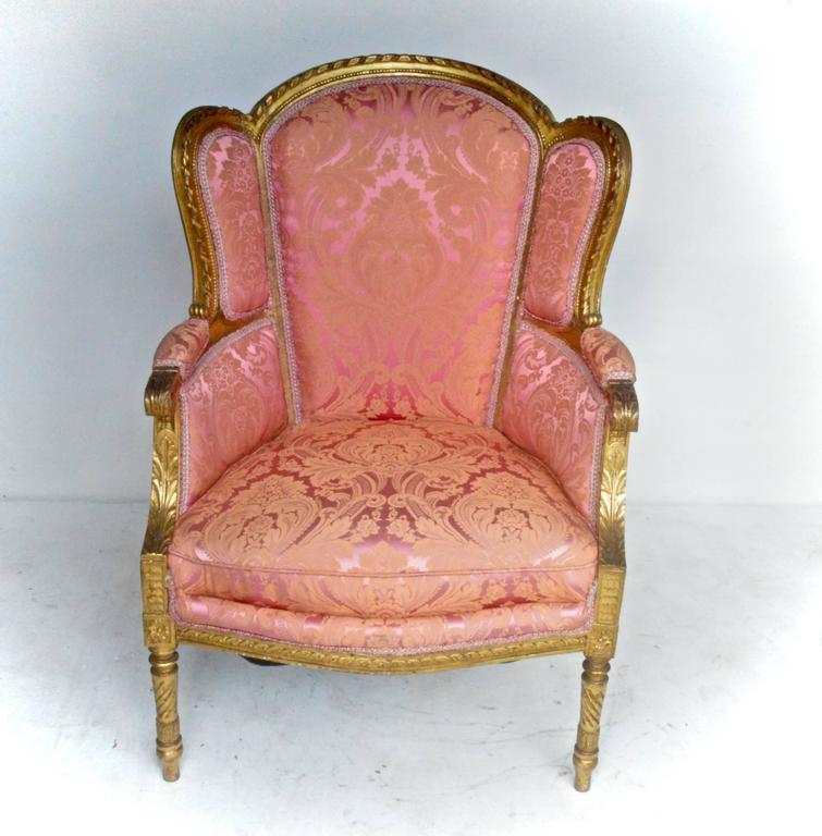 19th century Louis XVI style bergere of carved Giltwood. The chair is dressed in a silk blended damask of playful pinks in the taste of Fortuny. Fabric appears to be from the 1960's upon inspection and is in good condition.