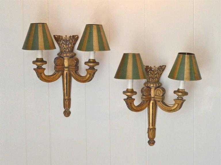 A superb pair of carved giltwood sconces in the Louis XVI taste. The pair are adorned by hand-painted tole' shades in green and gold. Electrified and in working order, these late 19th century sconces will transform any space in which they are