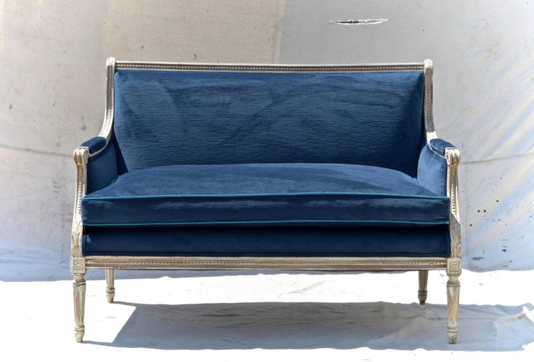 A stunning pair of Louis XVI style settees in navy velvet. Custom finished grey frames support plush and reconditioned single long down cushions on each love seat. Cushions are outfitted with a subtle contrasting pipping in peacock velvet.
