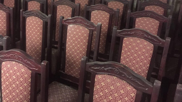 50 pieces of vintage red wooden dining room chairs. Fabric seat and back. Red Bordeaux fabric with flower leaf kaleidoscope pattern. Late 20th Century. Solid furniture perfect for hotel, food and beverage, catering business, library, meeting