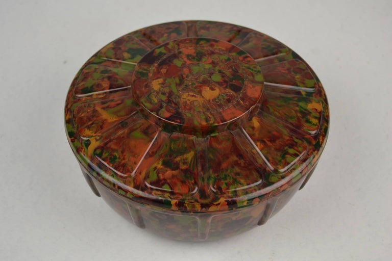 Stylish  Art Deco Bakelite Bonbon Box for the Belgian Chocolate Brand Martougin.  This Storage Box for Chocolate dates from the 1920s and is made in the beautiful Autumn Colors red, brown, green, orange and yellow with a Flamed Pattern. On the lid