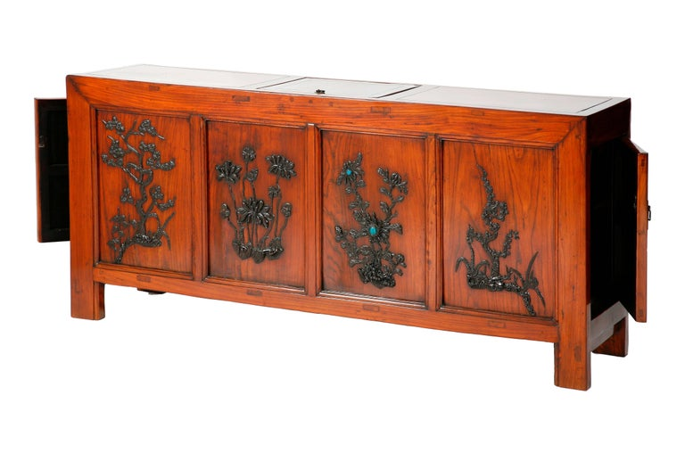 The unique square corner coffer with a lift top and doors on both sides for accessing to the storage spaces, rectangular-sectioned frame members carved with molding, the front panels inlaid with ebony carvings of pine, lotus, chrysanthemum with