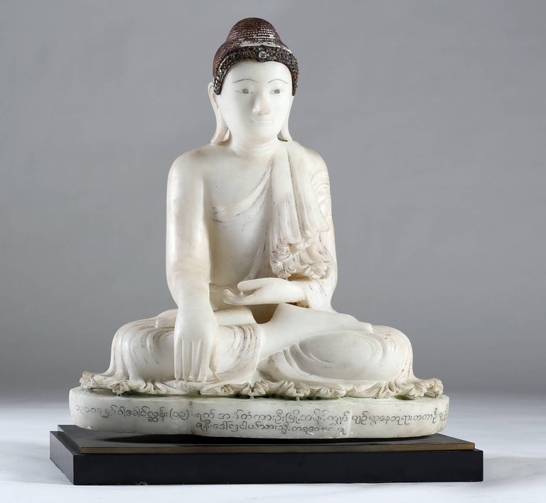 Seated in virasana on a shaped base, his right hand in bhumisparshamudra, the finger tips of the right hand touch the earth to symbolize the moment of enlightenment, the left on his lap.  The robe leaves the right shoulder uncovered, finely carved