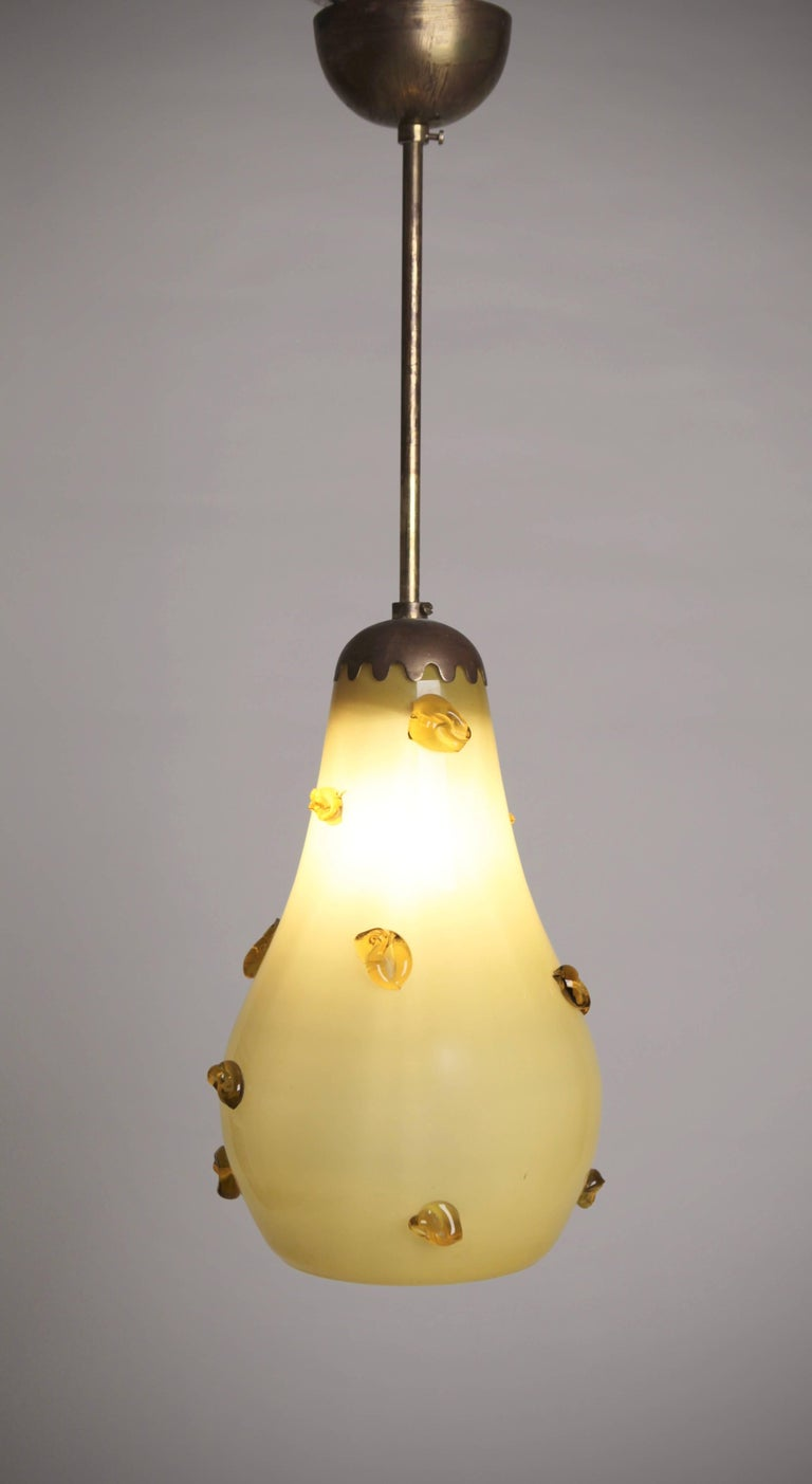 A pear shaped over-coated yellow glass with ceiling light, with melted glass drops and brass fittings, in the style of Paavo Tynell, manufactured in Finland, circa 1940s.