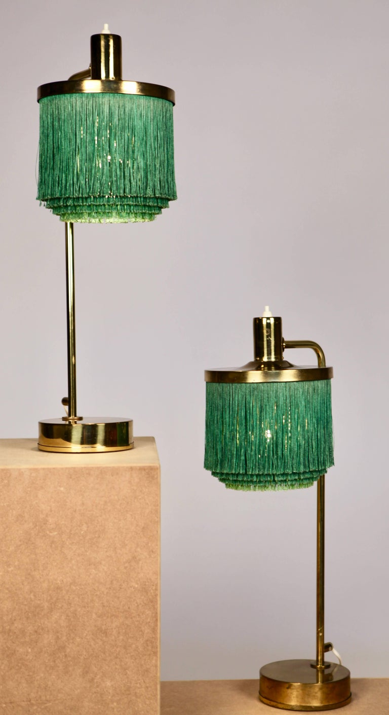 Great pair of table-lamps model B-140 by Hans-Agne Jakobsson, manufactured in Markaryd, Sweden, 1960 Bottle green silk fringes and nice patina to the brass Both signed with paper label.