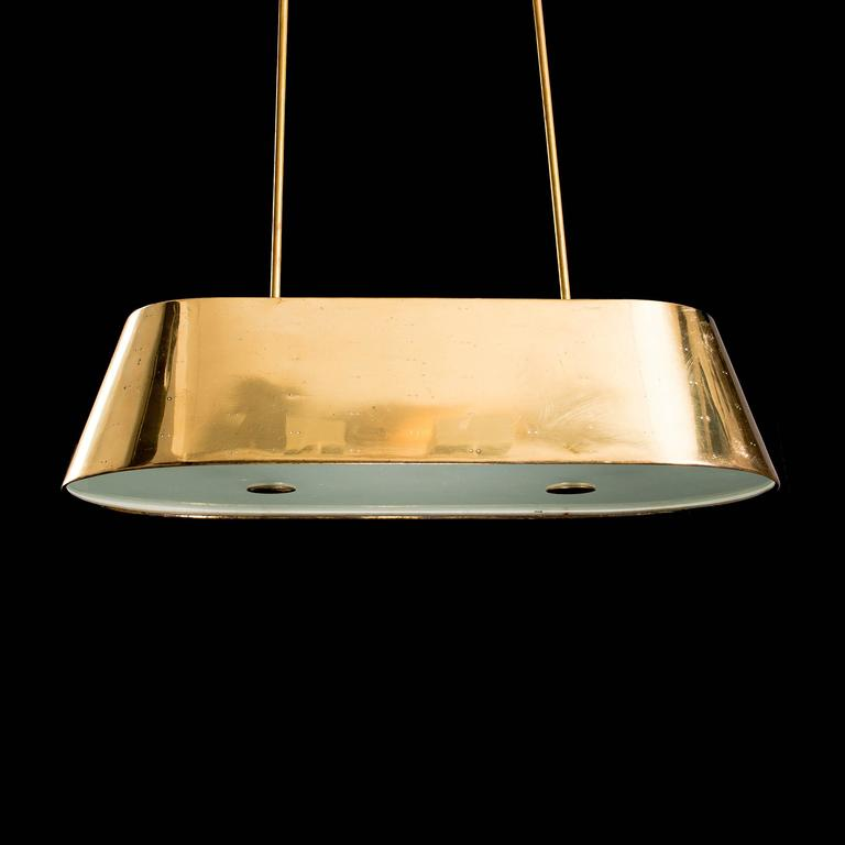 Rare and large Paavo Tynell ceiling light.  Perforated brass and glass.  All original.  Finland, 1950s.