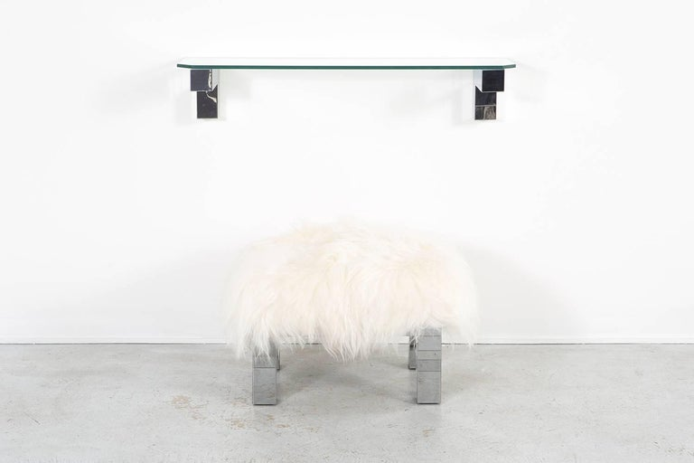 """Floating shelf and stool set  designed by Paul Evans for Directional  USA, circa 1970s  chrome and glass with the stool reupholstered in Mongolian sheepskin  shelf 12 ½"""" H x 46"""" W x 12"""" D  stool 18 13/16"""" H x 26 ¾"""" W x 20 ¼"""""""