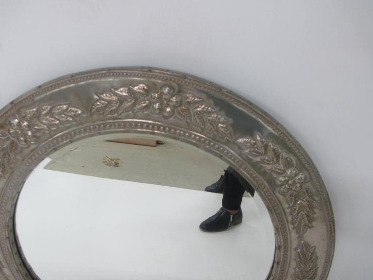 """Round metal-clad mirror.  28"""" diameter with clear mirror in centre. Frame in tin metal clad with slight age look."""