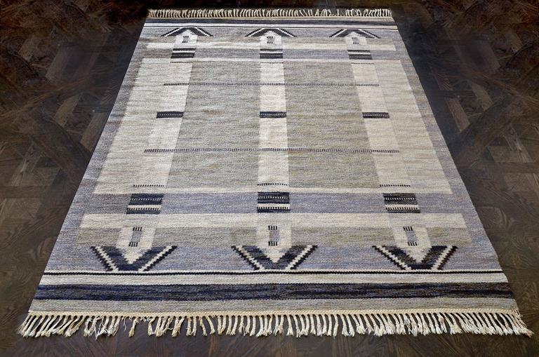 This vintage handwoven Swedish rug has a sandy gray field interrupted by triple ivory stripes with charcoal stepped half-lozenges at each end, capped by charcoal and ivory stripes at each end. Signed by the original artist and workshop.