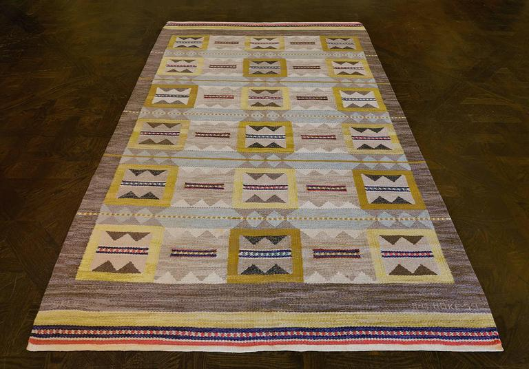 This traditional hand-woven Swedish rug has a shaded gray field of serrated panels playfully alternating with bordered, serrated, and banded cells, separated by steel blue banded rows, in a shaded charcoal border, various delicate stripes at each