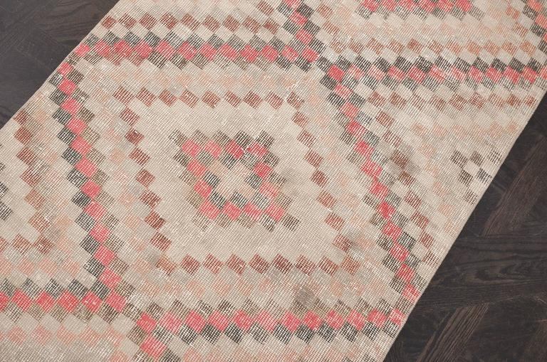 This handwoven Turkish deco rug has a lively beige field with central column of polychrome celled stepped lozenge medallions, with similar vibrant motif at each end. In order to soften the colors of this rug it has been antique washed. Originally