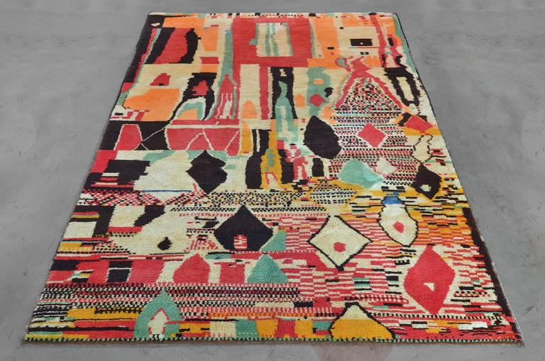 Late 20th century, hand-knotted wool rug from Morocco features an expressive collage of rectilinear color blocks, abstract checkers, and stripes densely patterned in a vivid combination of turquoise, rose, coral, citron, orange and coal black with