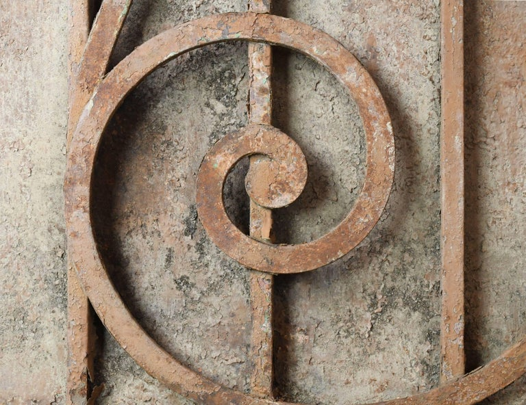 This gorgeous, heavy iron door/gate features decorative scroll work on one side and solid panels on the other. Beautiful finials at the top add a touch of grandeur. This piece is in good condition with peeling and rust typical for a 100+ year old