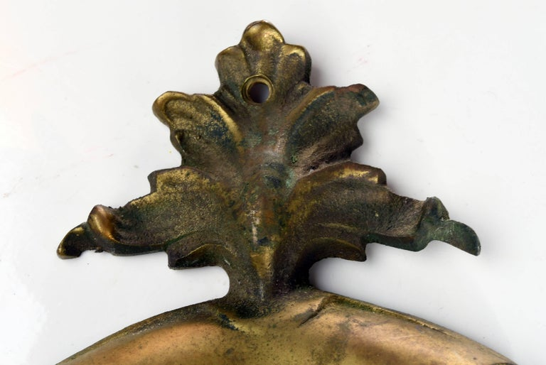 This cast brass door knocker is decorative and designed with floral elements. In the middle of the plate, the letter