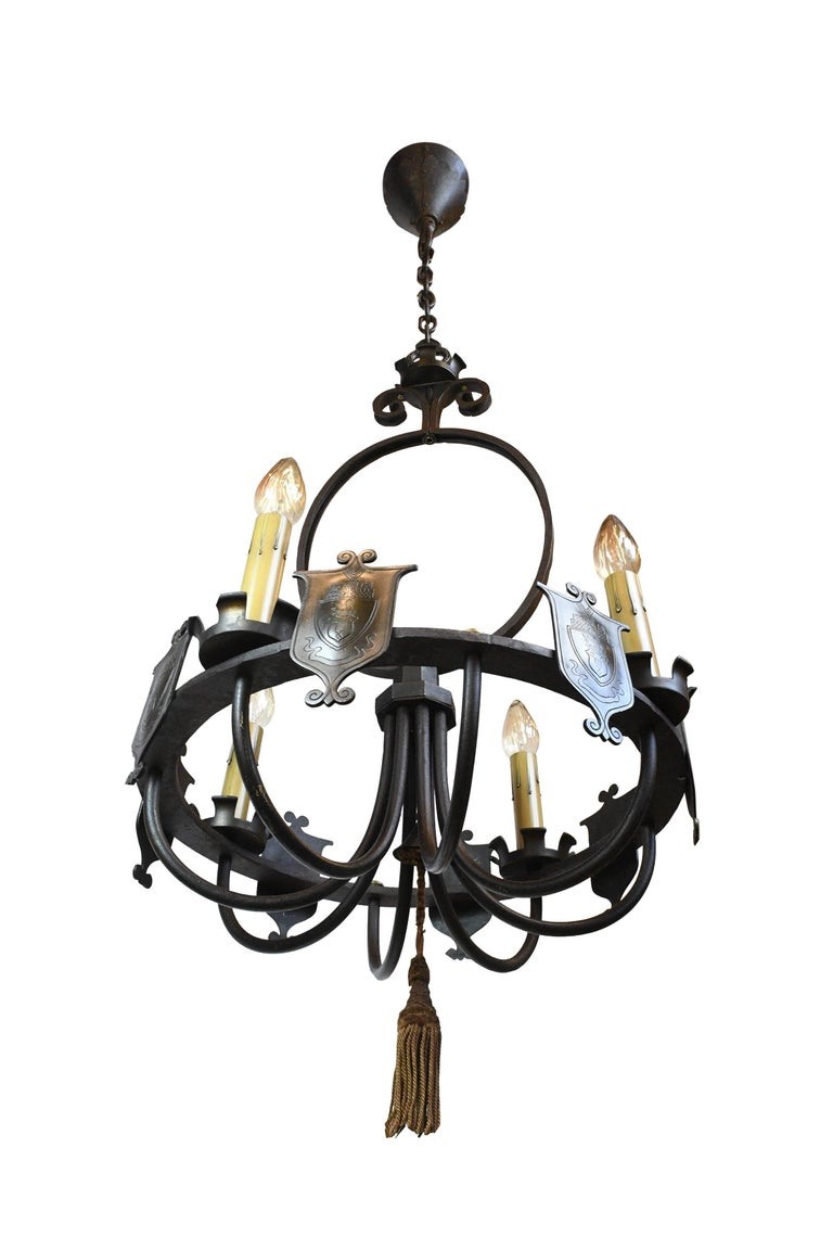 Decorative shields add a royal touch to this large iron chandelier, and sweeping, curving lines give a sense of elegance. This fixture would make a stunning addition over a dining room table, or as a focal point in a large space.  We find that