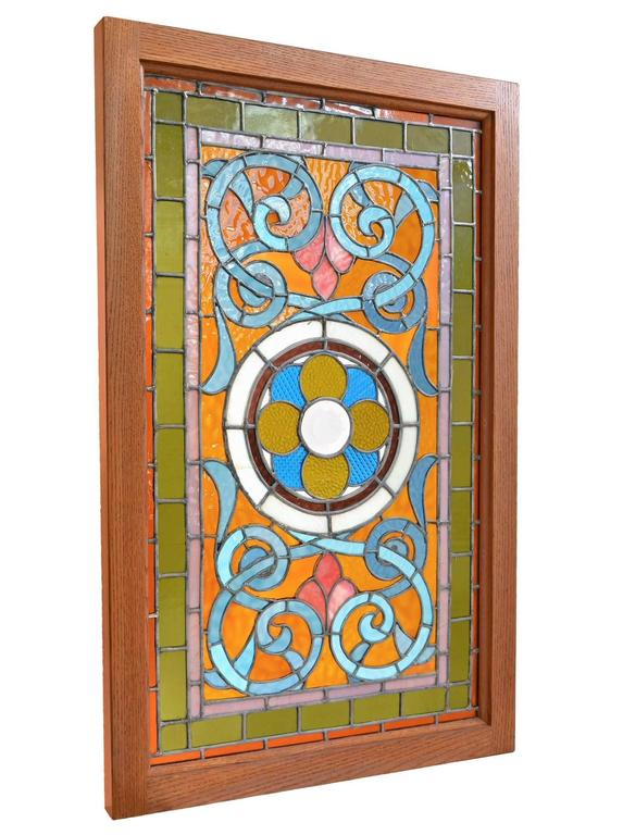 This beautiful Victorian stained glass window features amber and teal blue glass, and has a lovely pattern that centers on a large beveled rondelle in the center. The colors are bright, cheerful, and extremely vibrant. We have four matching windows