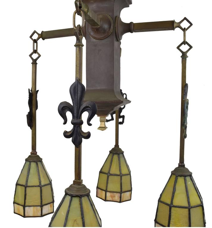 """This fixture shows the many facets of the Arts and Crafts era with a medieval  motif indicated by the emblems on each of the chains and lovely, stained glass shades.   Overall, the fixture is 26"""" tall x 18"""" wide x 18"""" deep.  We find"""