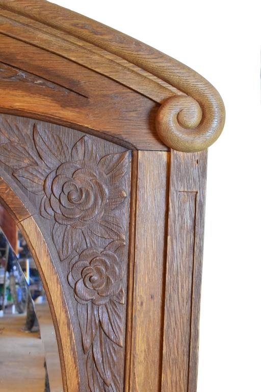 This carved oak frame features floral rose motifs and oval mirrors with bevelled glass. Each is in pristine condition. Matching pair available.