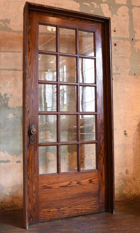 These divided fifteen-light oak doors are in good condition coming from a school house. Original finish, in their original jambs, their original ball tip hinges and original brass hardware. Will let lots of light into your room and there are 4