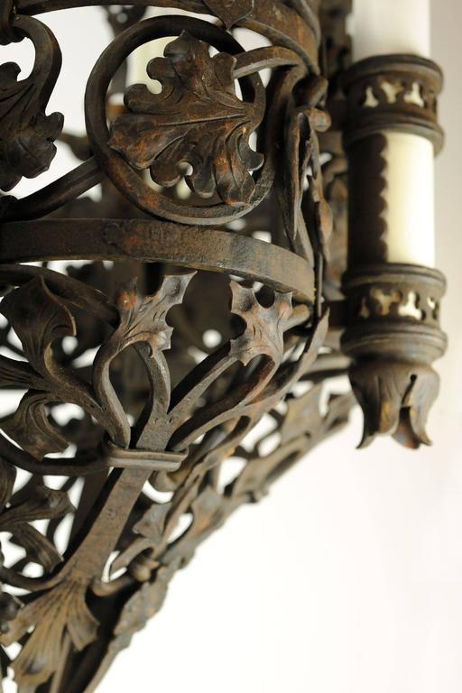 This wrought iron Tudor chandelier is truly a feast for the eyes. Leaves of varying shapes and sizes wraparound the fixture, giving it an organic, earthy feel, accentuated by thick strands of twisting, coiled iron. The four candle covers sit atop