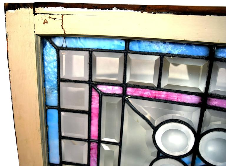 This wonderful, unique curved Victorian window features beveled glass clam roundels, surrounded by beveled glass squares and rectangles, and beautiful pink and blue stained glass that add exceptional pops of color. This window is truly one of a kind