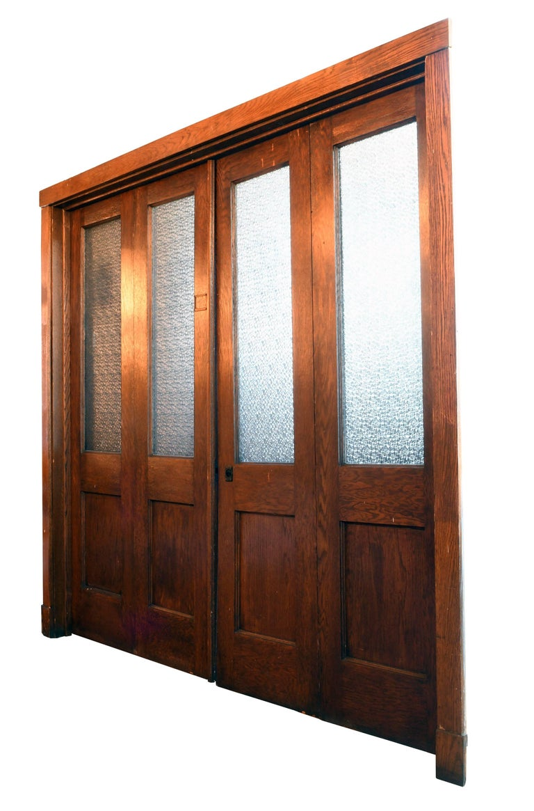 These handsome bi-fold doors originally came from a school in Youngstown, Ohio. Made of oak and stained a rich brown, the wood is in excellent condition. This is noteworthy, considering that the doors spent nearly a century in a school among