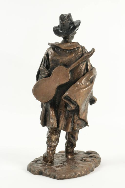 Sculpture of a typical person living at the butte Montmartre in the 19th century. Guitar player in metal.