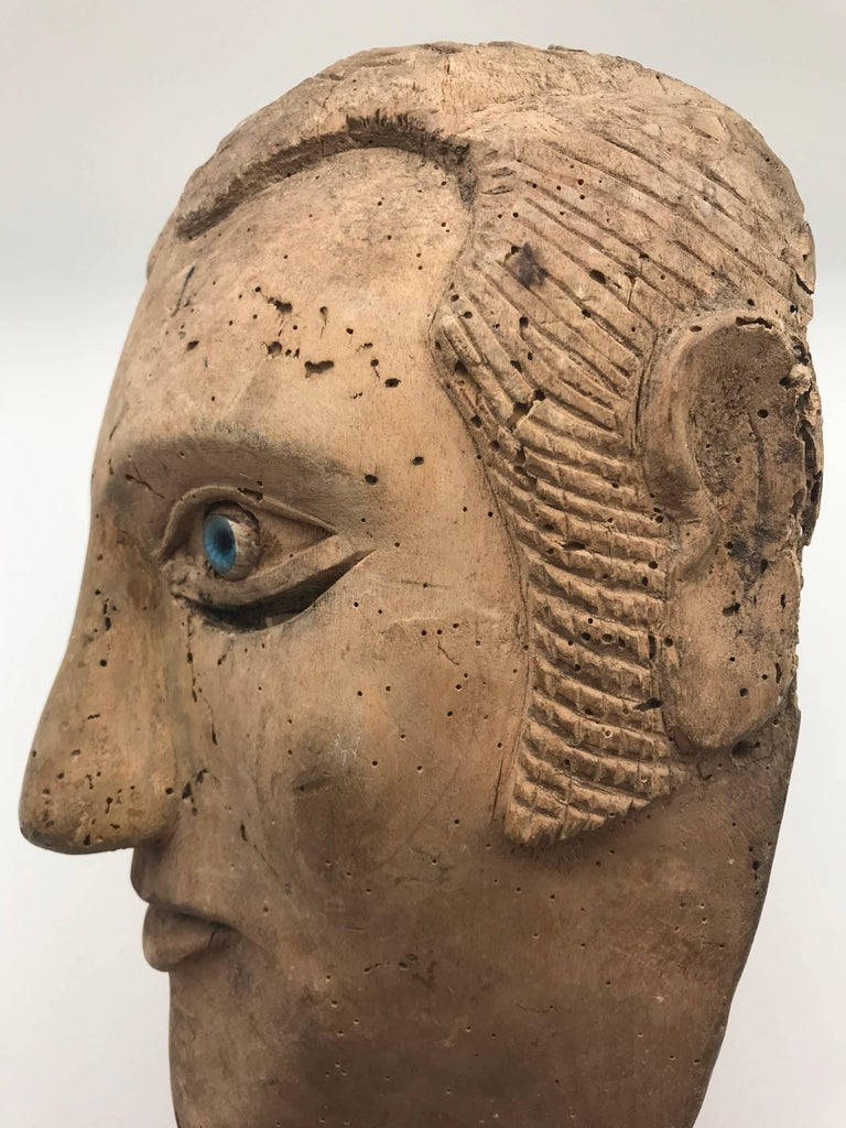 Unique carved mask made by a slave, depicting his or her master. Over enhanced facial features are apparent while blue glass eyes distract from the slits where the user would see through.