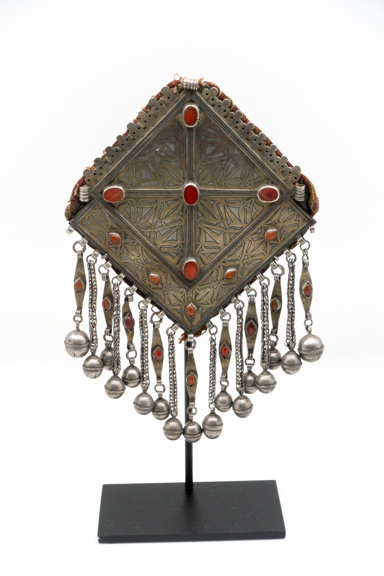 Antique silver pendant from the early 1900s Turkmenistan. Hand-tooled coin silver with hanging bells and over 40 carnelian settings, mounted on a custom metal, black painted base.