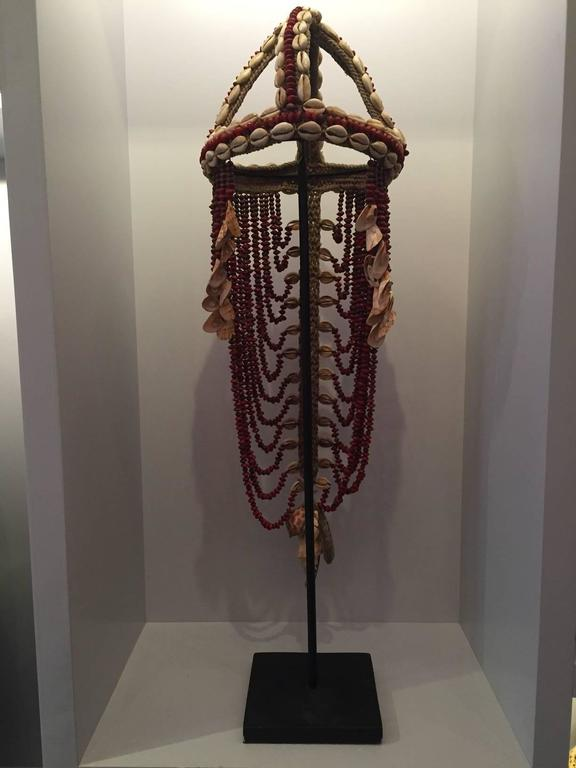Headdress from Papua New Guinea made from cowrie shells and red seeds applied to traditional macramé fiber. Traditionally this type of ceremonial headdress also served as a form of currency and was often included in wedding dowries. The monetary