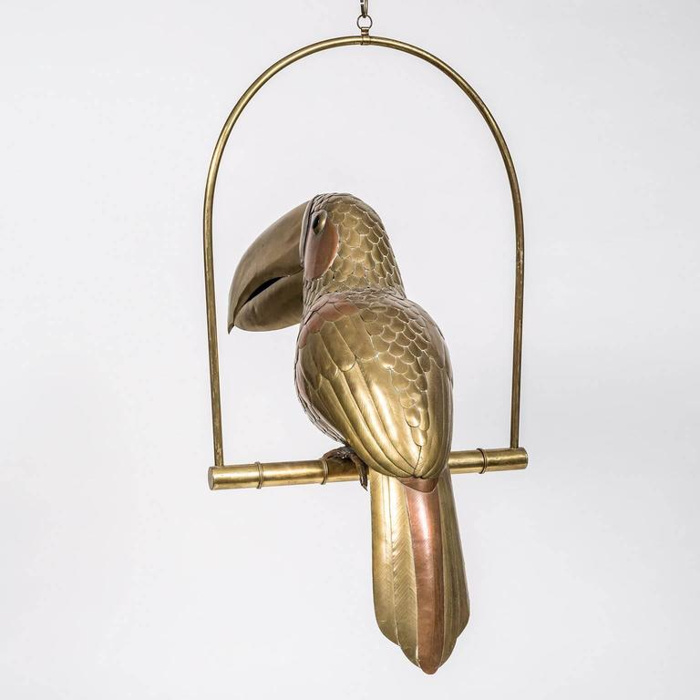 Sergio Bustamante brass and copper perched parrot with glass eyes and 11 inch brass chain to suspend from the ceiling. Executed in the 1980s by the renowned Mexican artist in his hometown of Guadalajara.