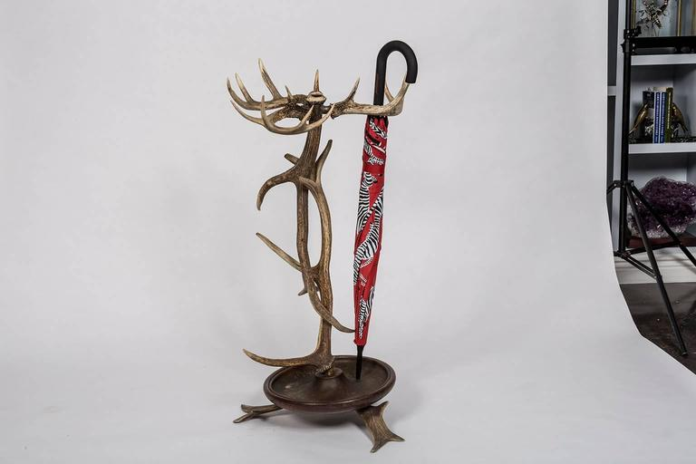 Black Forest style Antler umbrella stand from a 1920s Adirondack Great Camp. The antlers are sturdily affixed to a metal lined wooden drip tray supported by three splayed antlers. This beautiful sculptural item from Mother Nature is not only