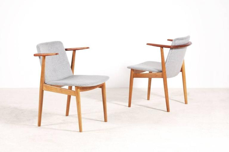 Very nice pair of teak and oak armchairs designed by Hans Olsen, 1950s.  Newly upholstered with a premium quality wool fabric. Excellent condition.  We ship worldwide.  Express delivery in one week anywhere in the USA for 550 Euros. (Full