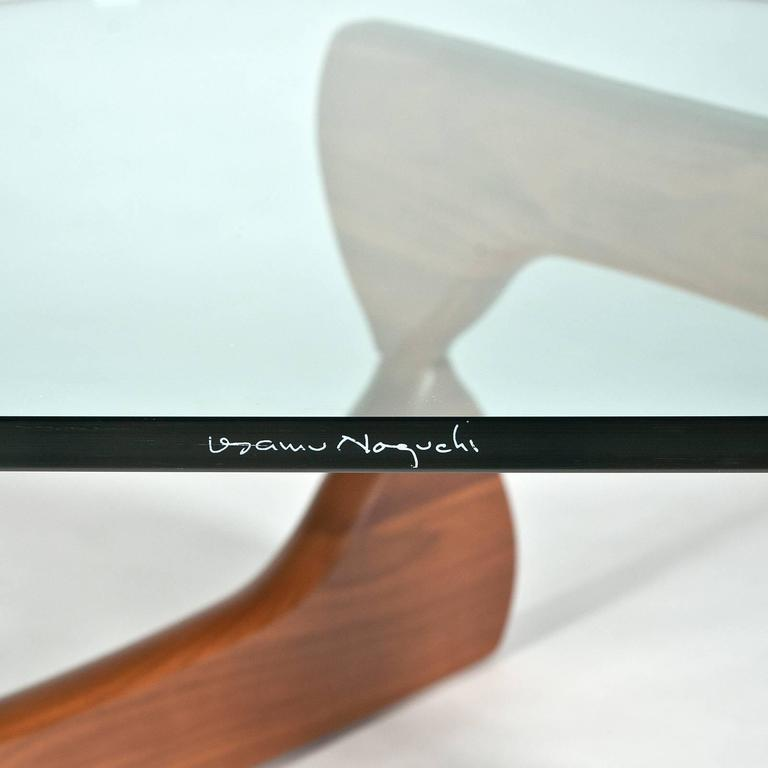 Designed in 1948. Made in the USA. Authentic table by Herman Miller. Note signature tag on bottom of base and etched signature on edge of glass. From circa 2010 production in very good condition with wear consistent with age.  An iconic table