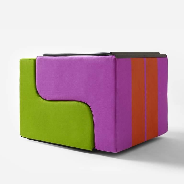 SOFO Armchair is a seat to place in a row, like a train, or to stack to build solid, colorful mountains. It is simply a block made with an S-shaped cut from a cube of polyurethane, covered with fabric featuring two large stripes. The result of a