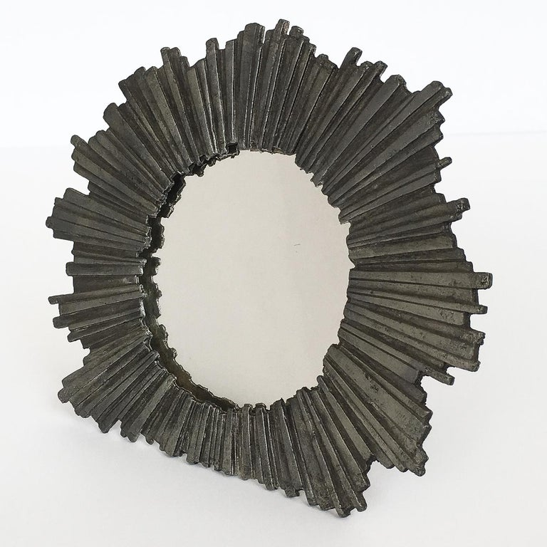 Brutalist Metzke pewter starburst framed mirror, circa 1978. Stylized solid pewter frame surrounds a small round mirror. Could also be used as a picture frame. Easel backing for table top use. The frame could also be hung on the wall using the small