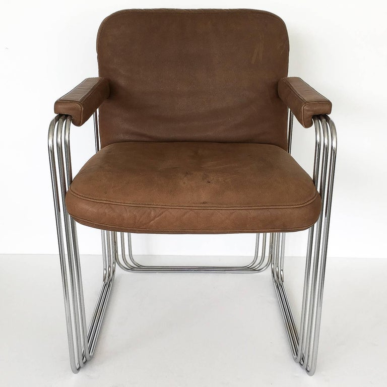 Set of six unique chrome frame and brown leather dining armchairs, circa 1970s. These chairs feature a stacked and stepped chrome-plated steel sculptural frame. The frame of the chairs creates a three dimensional cage-like rectangular frame on three