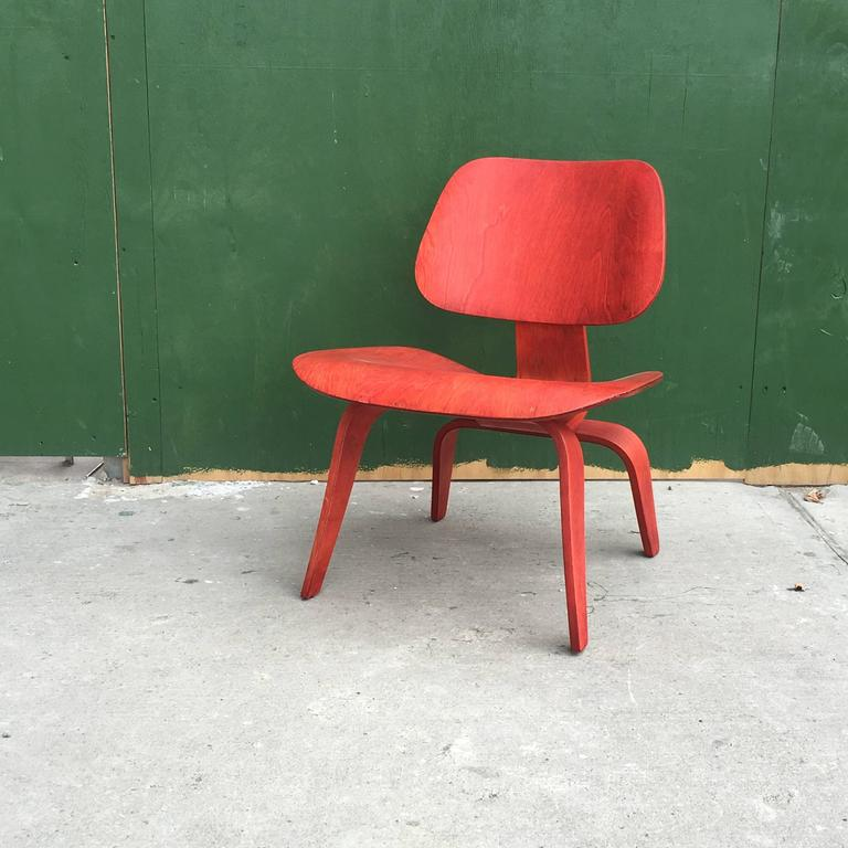 Early Eames LCW manufactured by Evans Products in the 1940s. Rare red version of the iconic chair. Chair is structurally sound and in great shape given age. Shock mounts reglued at some point. Bright vibrant red aniline dye on birch veneers.