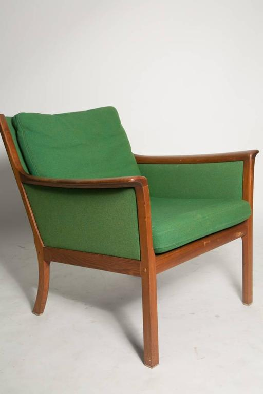 Ole Wanscher Japan lounge chair. Sculptural teak armchair with navy green and emerald green two tone fabric designed by Ole Wanscher for Poul Jeppesen during the 1960s. The design is an interesting combination of elegance and fun.