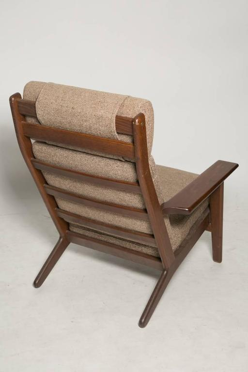Great vintage high back lounge chair designed in 1953 by designer Hans J. Wegner for GETAMA. Smoked oak and brown wool fabric. Iconic chair of the Mid-Century Modern.