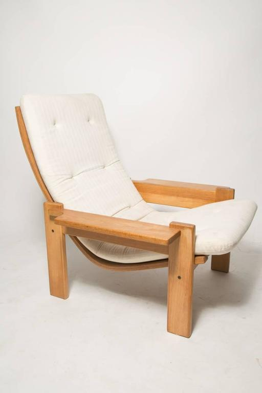 Extremely rare and generously proportioned pair of plank arm lounge chair with curved backrest and stripe textured white fabric from designer Yngve Ekstrom for Swedese. Produced during the late 1960s. Brand's mark underneath the chair. These pair is