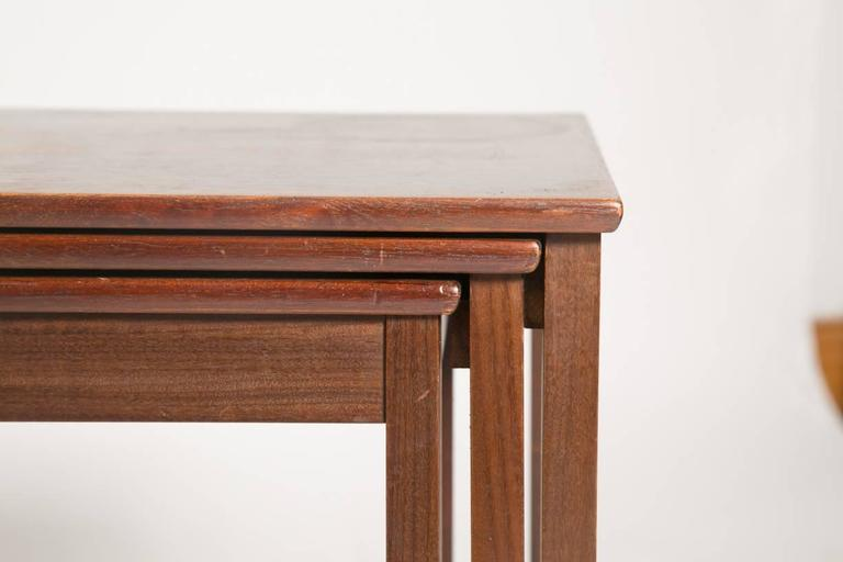 Sturdy banded square legs of old growth Brazilian rosewood support this set of nesting tables. The grain and chunky design give the nesting tables a club style. Each nesting tables fits into the next on rails. The tables are in good condition with