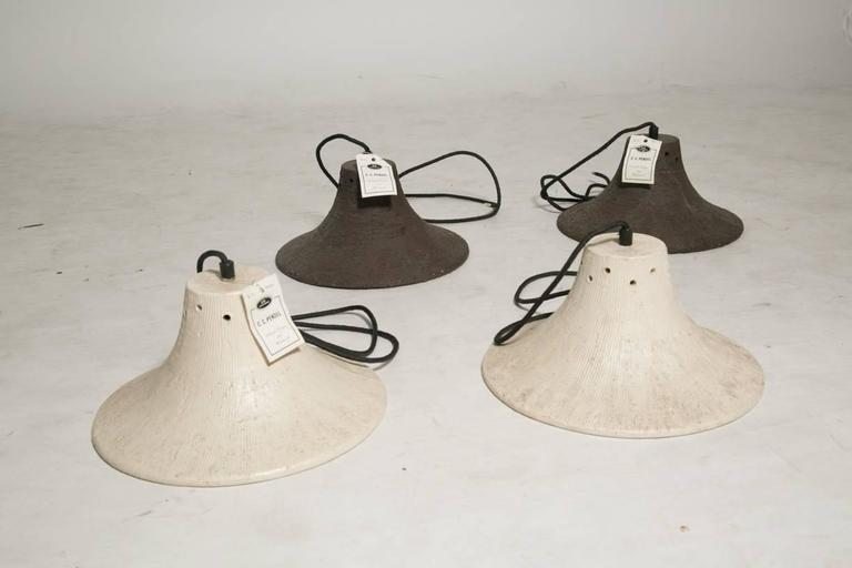 Vintage Studio Pottery stoneware light fixtures. two in textured earth with vibrant red enameled interiors and two in bone and earth with red enameled interiors. these lights are dead stock never installed with tags in place. elegant and rustic