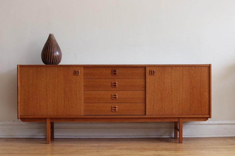 """Midcentury Danish modern teakwood sideboard. Just imported from Denmark and refinished! Four dovetailed drawers in the center flanked with sliding cabinet doors. Cabinets hold removable shelving. Excellent vintage condition!  Measures: 72"""""""