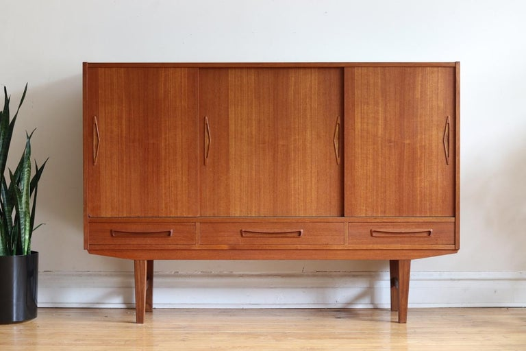 """Mid-Century Modern Danish Modern tall teak wood credenza. Just imported from Copenhagen! Sliding cabinet doors hold adjustable shelving.  Three dovetailed drawers. Triangle/arrow shaped handles. Excellent vintage condition.  Measures: 64 3/4"""""""